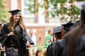 A female student smiles while walking down the aisle at graduation financial aid