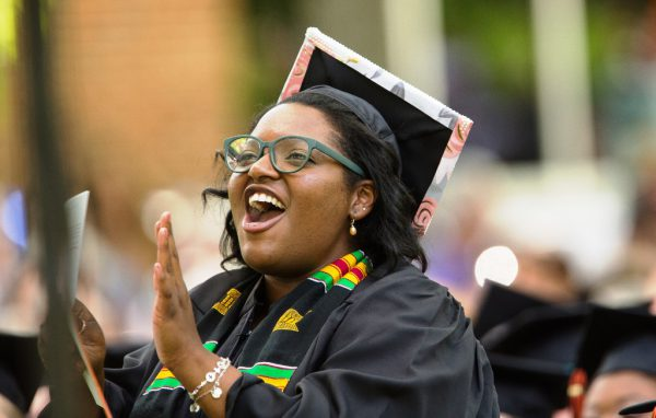 A student cheers at graduation disbursing financial aid