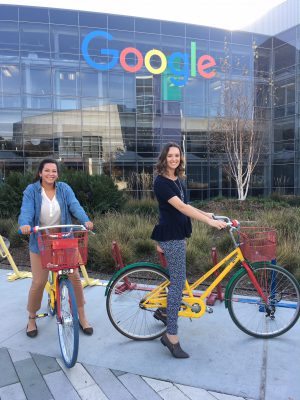 Two students on bicycles in front of the Google headquarters