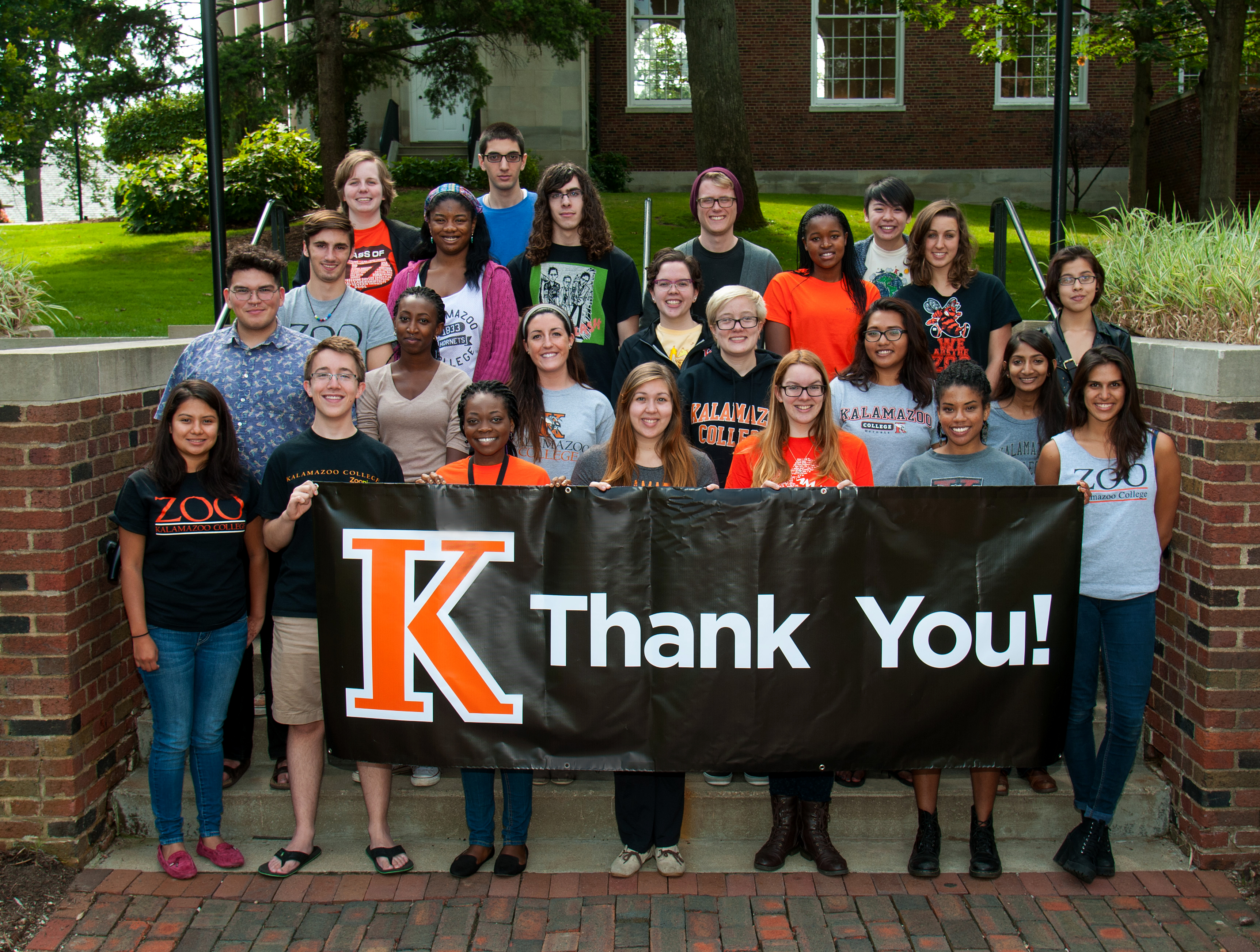 Kalamazoo College student phonathon callers holding a Thank You banner.
