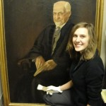 Eeva Sharp '13 squatting beside a spainting of a distinguised looking older man