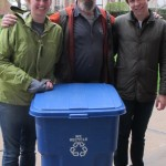 Two students stand beside an older man who's bottom half is covered by a blue recycling bin.