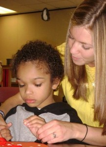 K student in civic engagement helps a child learn