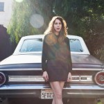 Author Rachel Kushner standing behind a car