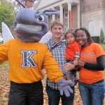 Two adults and a baby standing with Kalamazoo College mascot