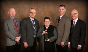 Five people standing with an award