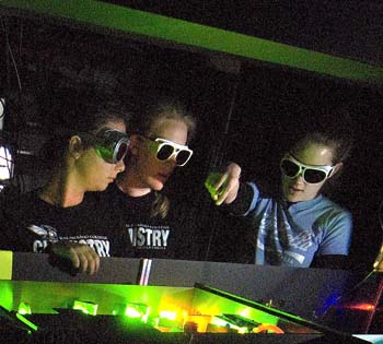 Three chemistry students wearing goggles in the laser lab at K