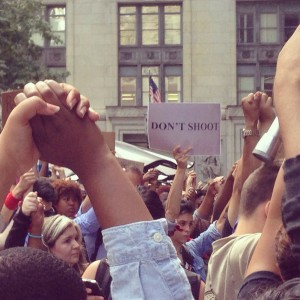 """brown hands held high in protest as a sign in distance reads, """"DON'T SHOOT"""""""