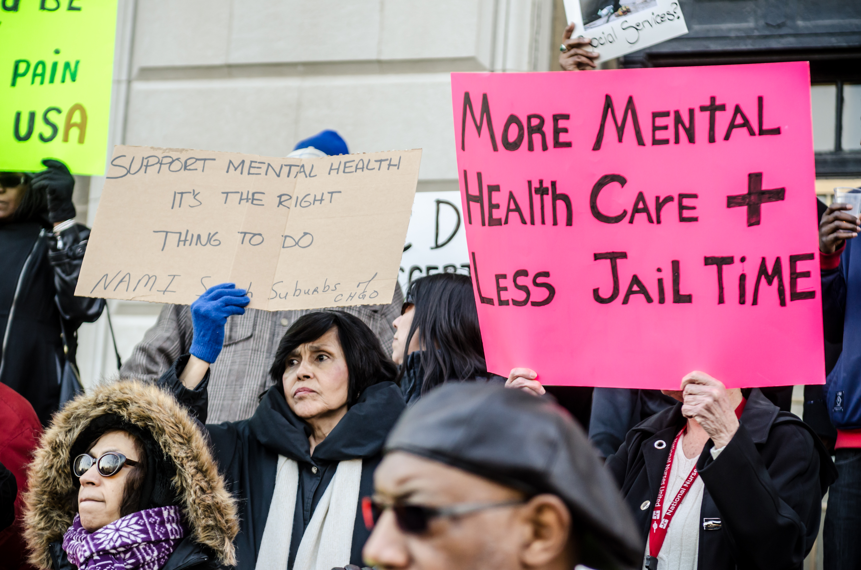 """protestor's signs that read, """"More mental health care & less jail time."""""""