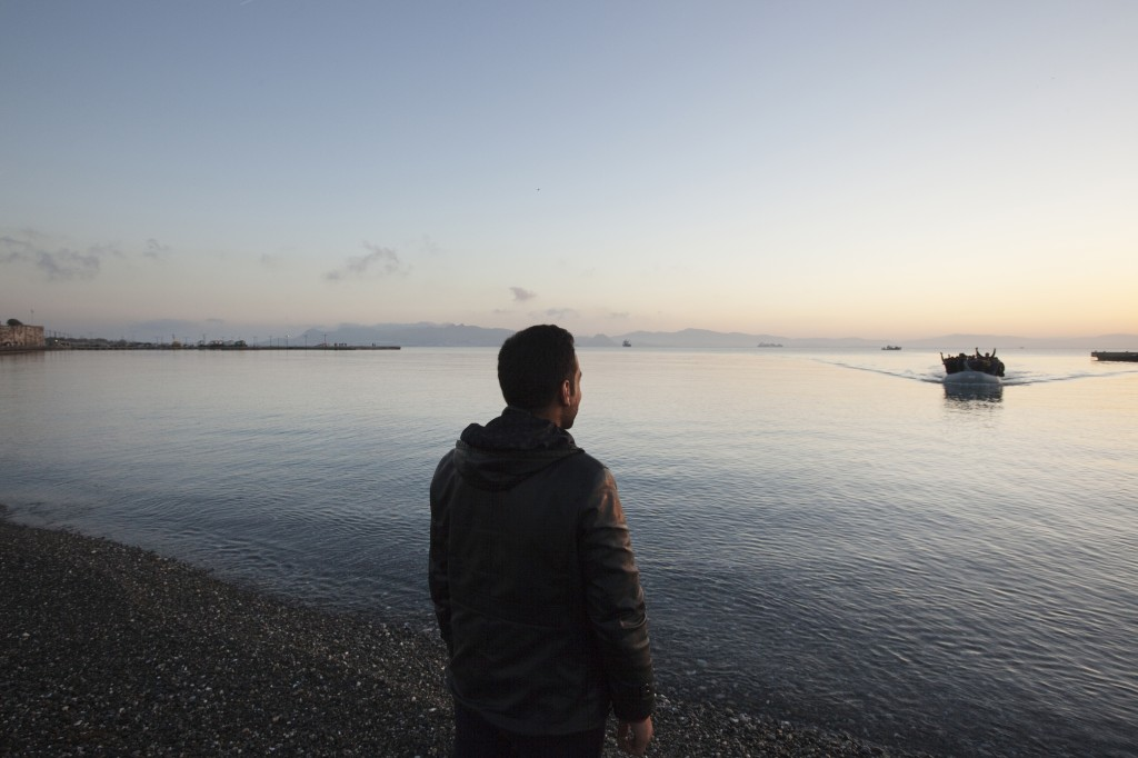 A silhouette of a man that stands right at beside a greek shore, a boat full of people are seen in the distance on the water as they arrive.