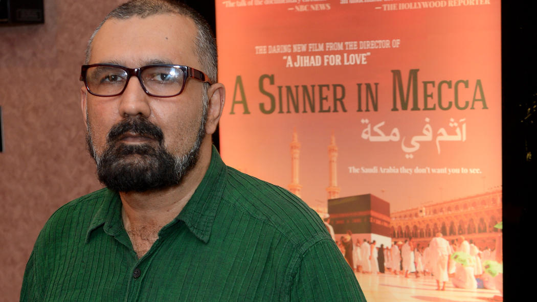 """Parvez Sharma in front of a movie poster for """"A Sinner in Mecca"""""""