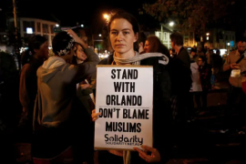"""protester with sign that reads """"stand with Orlando. Don't blame Muslims"""""""
