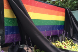 rainbow flag with black curtains draped over it