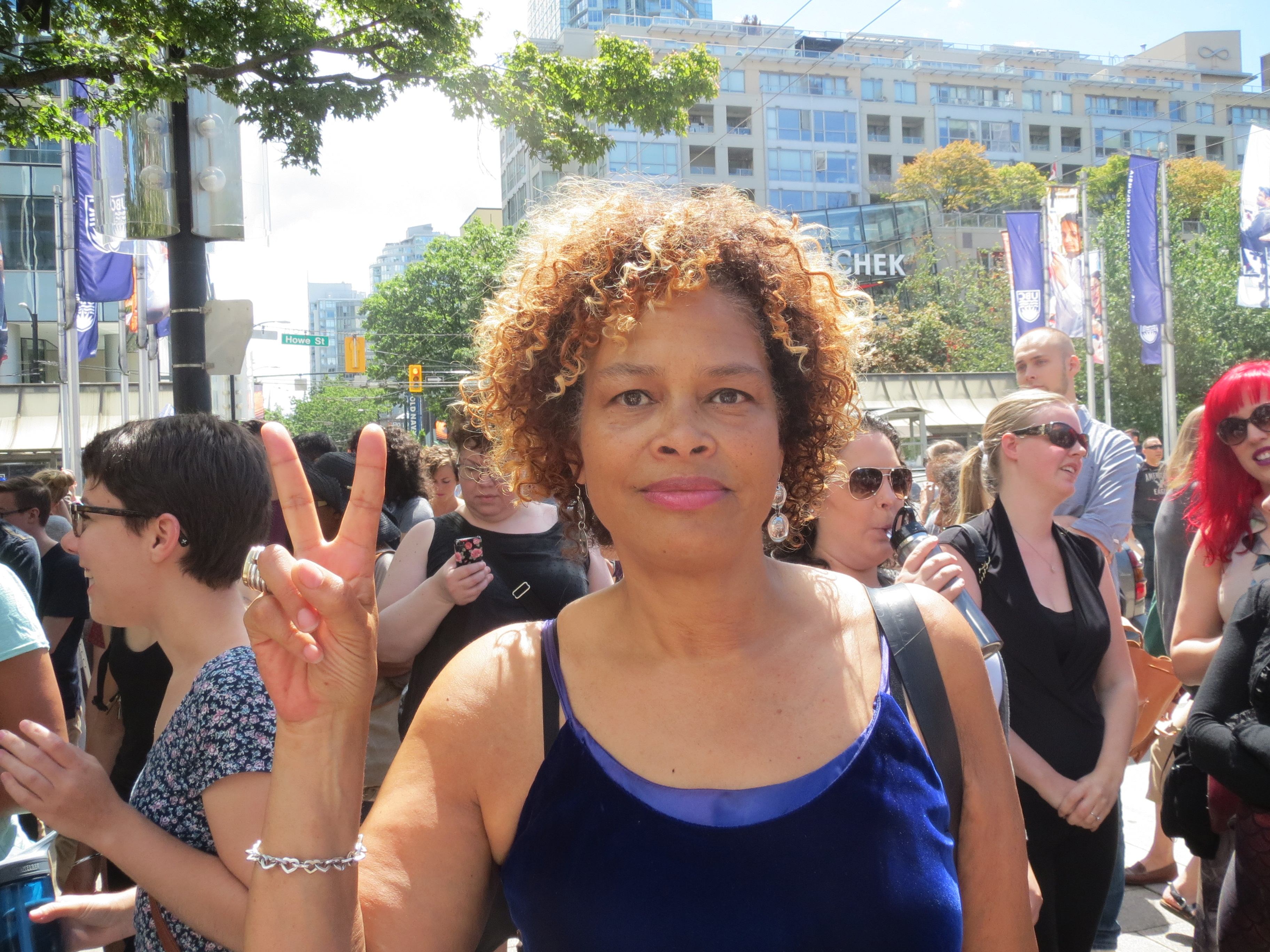 Constance Barnes holding up a peace sign surrounded by a crowd