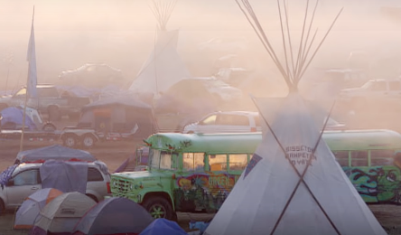 tipi in front of green school bus at Standing Rock Protest