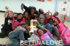 A group photo of Bettina Love and group of children making silly poses on the floor.