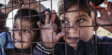 Two distressed children looking through a fence