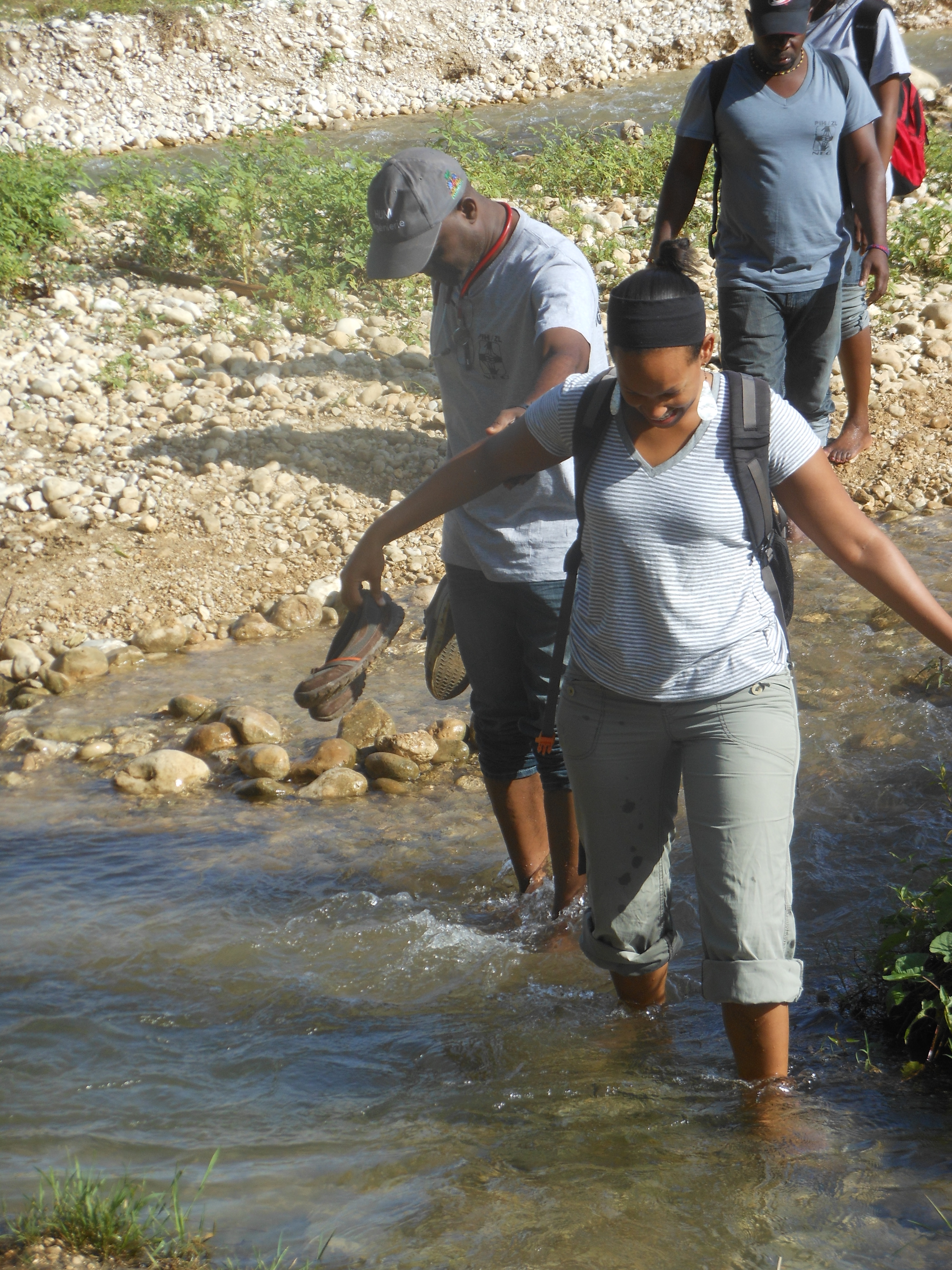 Drs. Michelle Morse and Fernet Leandre leading a medical team through a river on foot to a busy mobile clinic in rural Haiti