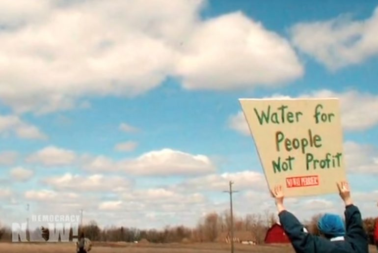 """Protestor holding sign that reads """"Water for people, not profit"""""""