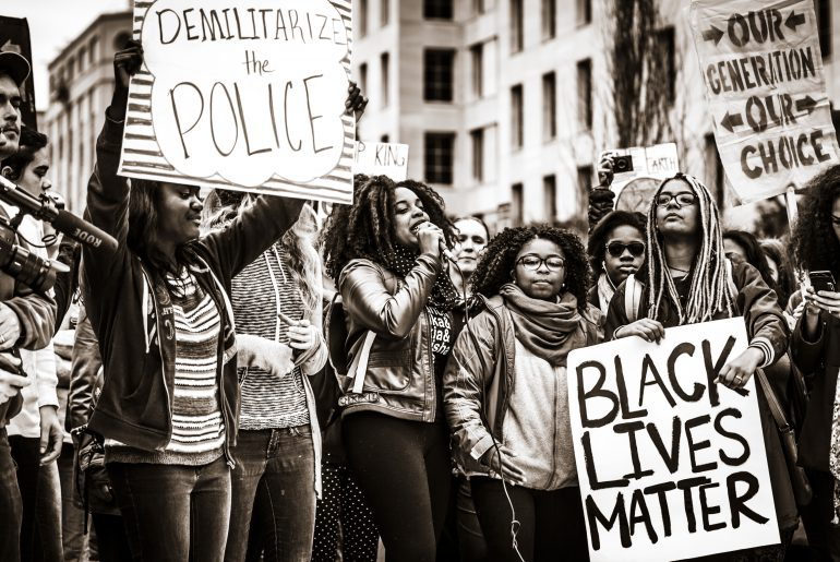 """Protesters with signs that say """"Black lives matter,"""" """"demilitarize the police,"""" and """"our generation, our choice"""""""