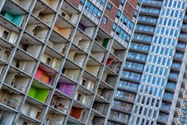 A partially demolished abandoned high rise with colorful walls next to a brand new high rise in Regent Park, Toronto