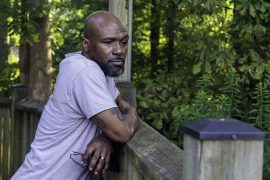 Black man leaning on fence post with a pensive facial expression