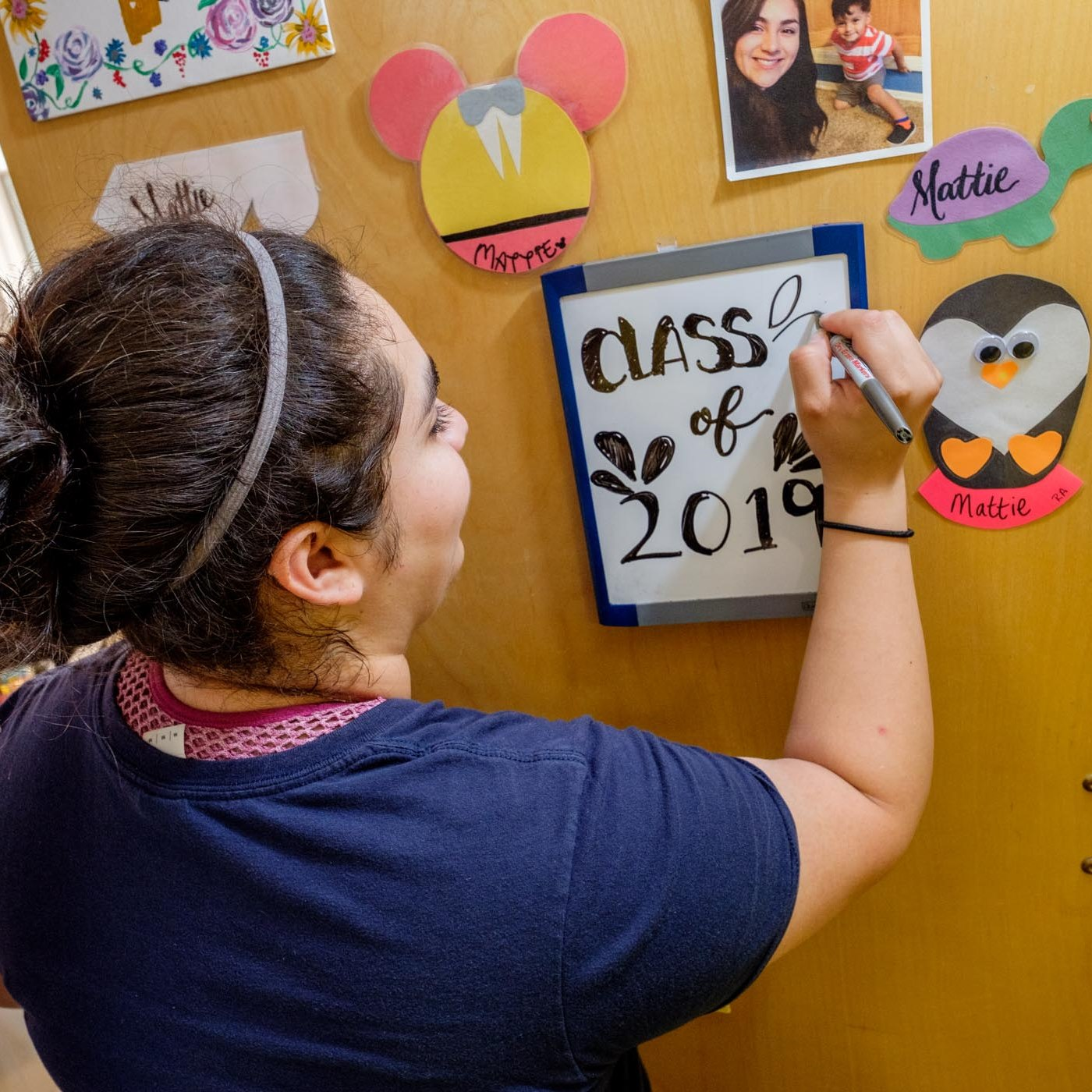Mattie Del Toro Writes Class of 2019 on dry-erase board for What to Bring to Campus Story